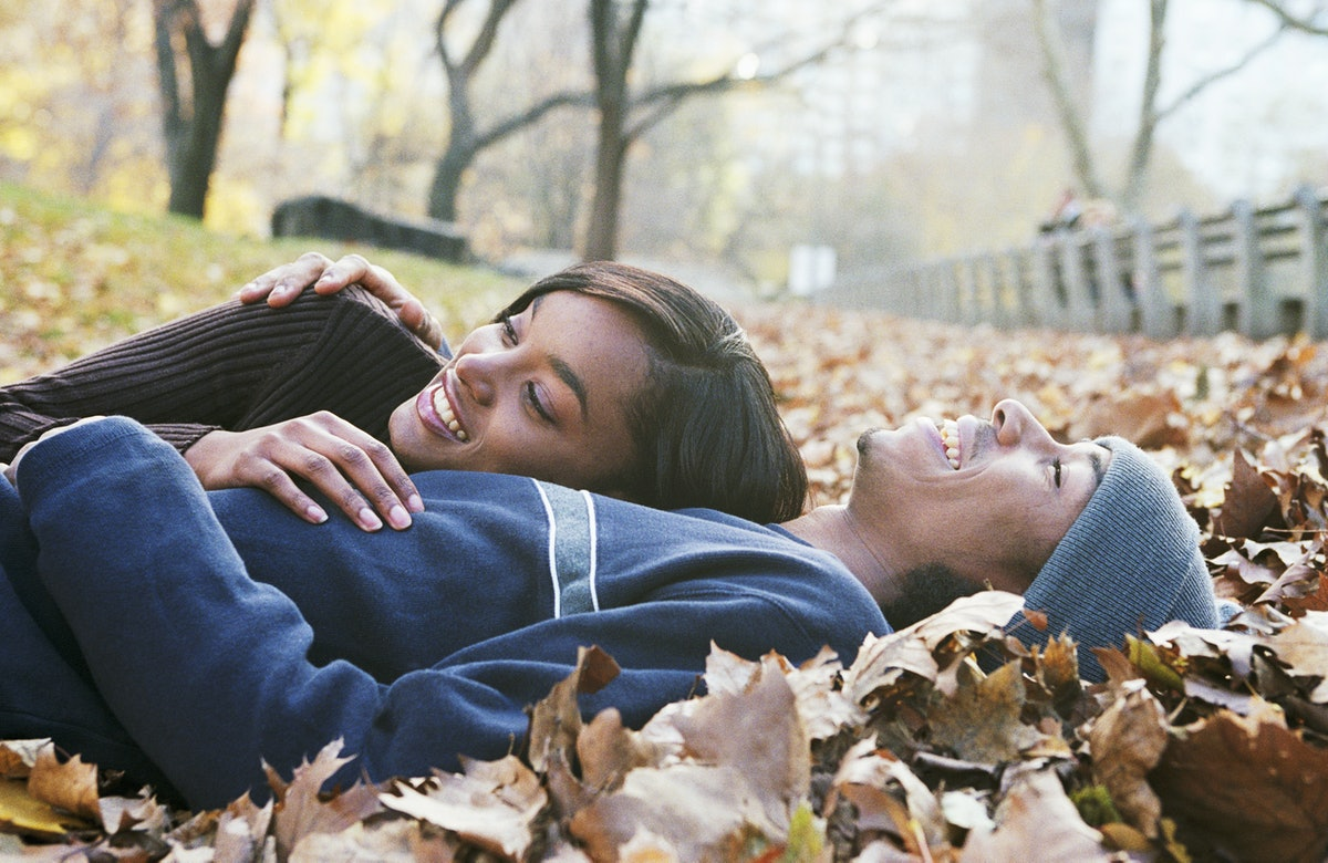 Young couple laying in fall leaves