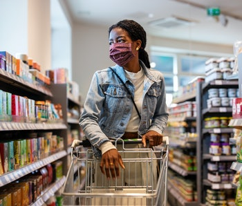 Customer with face mask shopping at a grocery store.