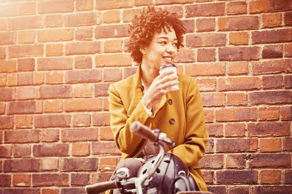 Young woman sipping coffee on bike