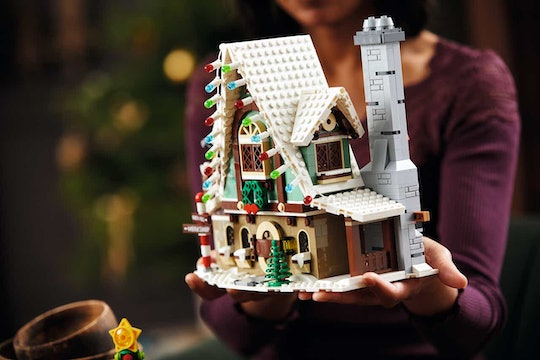 An image of a woman in an aubergine sweater holding a LEGO Elf Clubhouse.