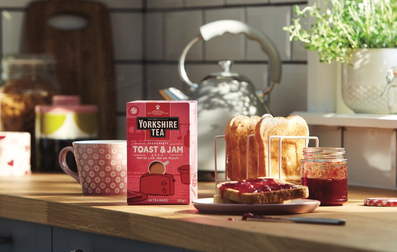 Yorkshire Tea's new jam and toast tea photographed next to a muck and a rack of toast with a plate of jam-covered toast in the foreground
