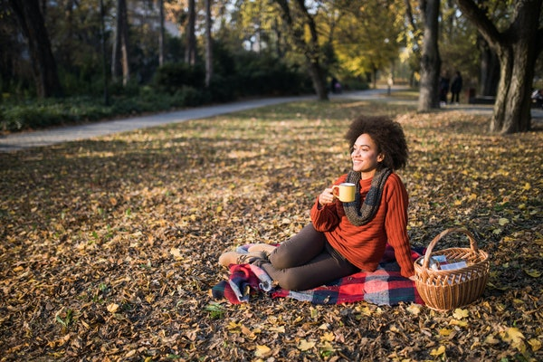 Young woman drinking coffee in fall