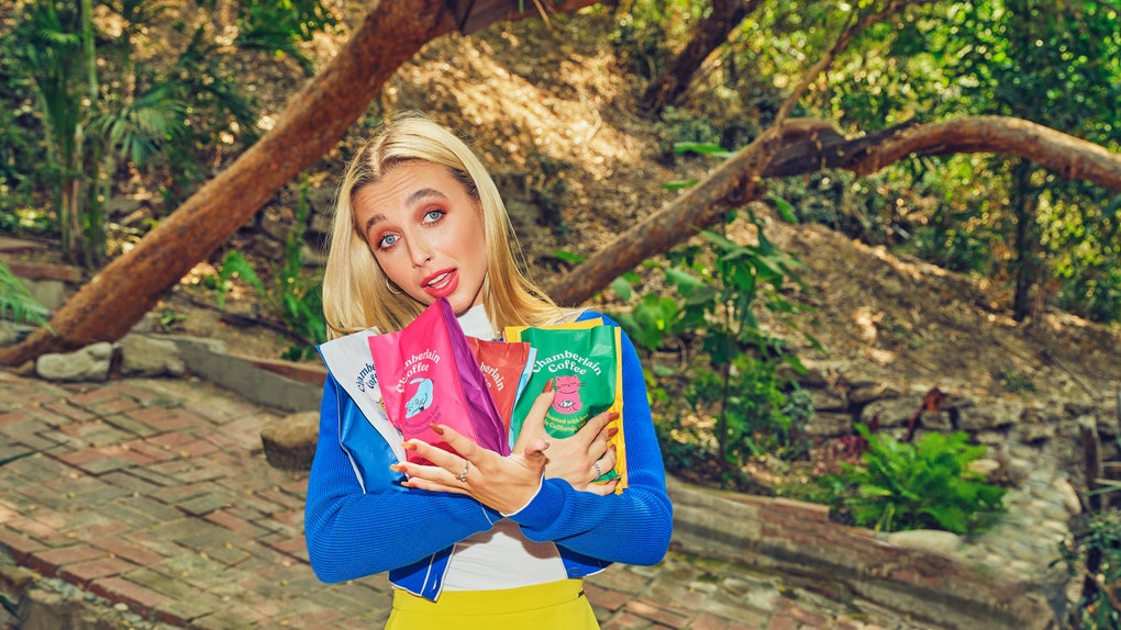 Emma Chamberlain poses in a colorful outfit while holding coffee bags from her new Chamberlain Coffee line.