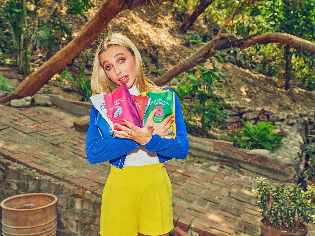 Emma Chamberlain poses in a colorful outfit while holding coffee bags from her new Chamberlain Coffe...