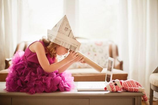 Child in newspaper hat looking through pretend telescope