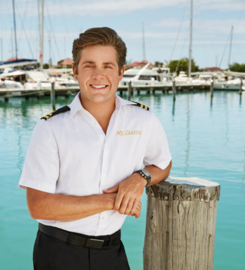 Eddie stands in his uniform in front of a marina with yachts moored on azure blue waters