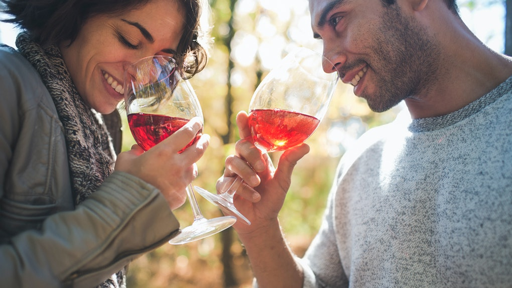 Young couple drinking wine in fall