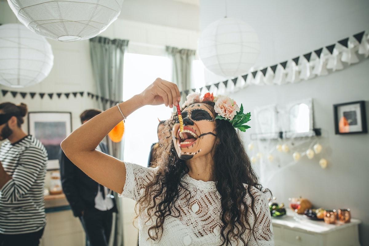 Young woman eating gummy worm on Halloween