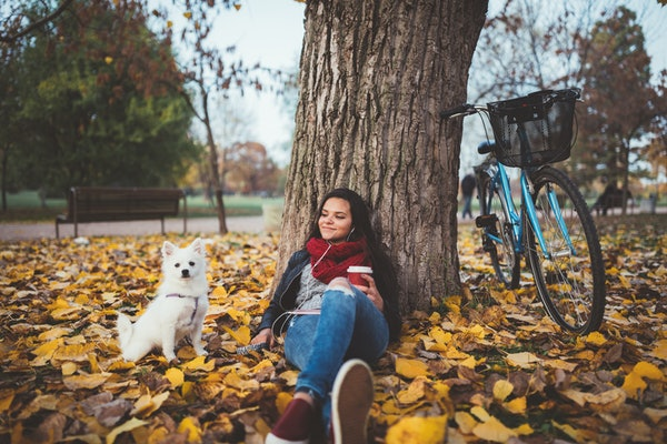 Young woman relaxing in fall leaves with dog and bike