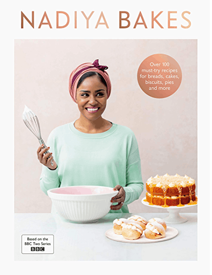 Nadiya hussein pictured on the cover of nadiya bakes wearing a mint green top, pink and purple head-wrap holding a bowl in one hand and a whisk held aloft in the other. A multi-tiered cake can be seen next to the bowl