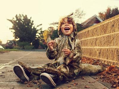little boy in dinosaur halloween costume sitting on street