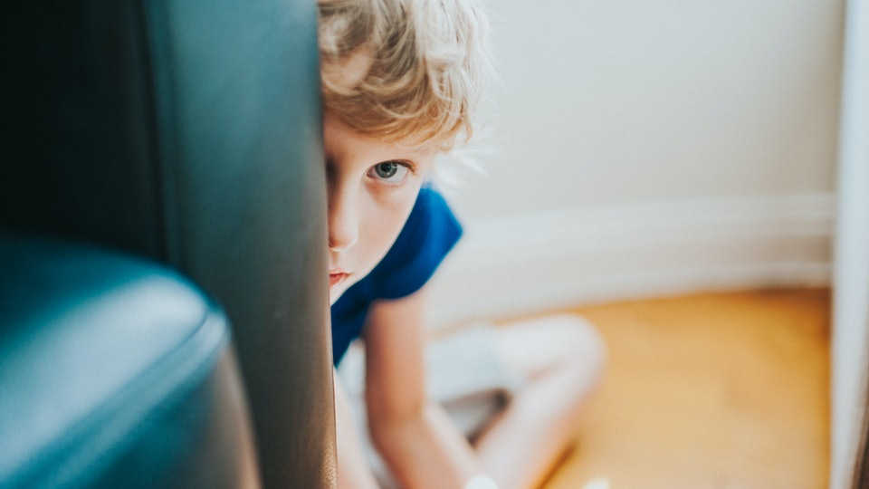 A little boy with curly blond hair peeks from behind a chair with an apprehensive expression.