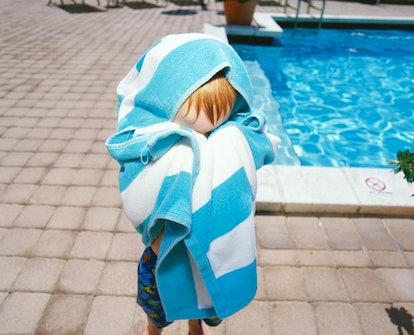 child hiding behind towel