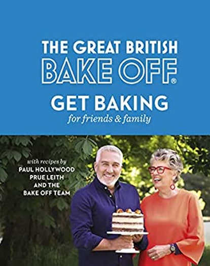 Paul Hollywood and Prue Leith stand in front of some trees on a sunny day. Paul is wearing a blue shirt and holding a multi-tiered cake on a stand, while prue is in an orange blouse with red glasses smiling and looking at Pauk