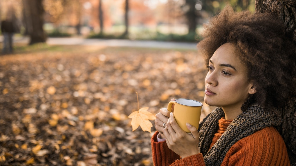 Young woman drinking coffee outside in the fall