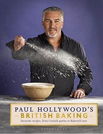 Paul Hollywood poses wearing a black shirt with a bowl of flour. He's dashing a fistful of the flour across the worktop while looking at the camera