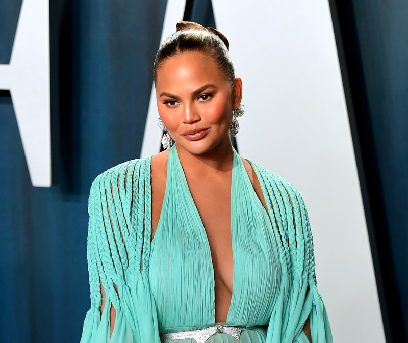 Chrissy Teigen pictured on the red carpet wearing a Tiffany blue dress with a diamond belt