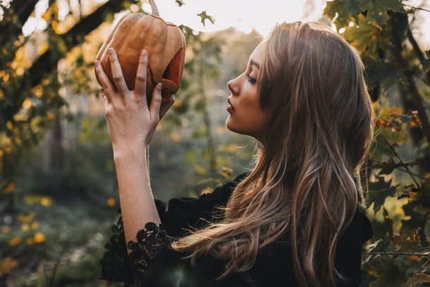 Young witch holding pumpkin