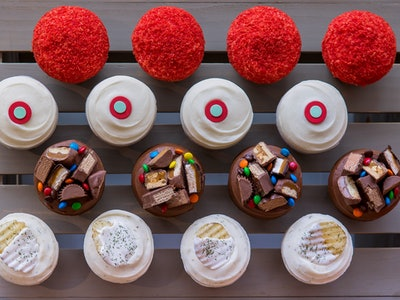 promotional photo for Sprinkles' Pregnant AF cupcakes, four rows of four cupcakes of each flavor