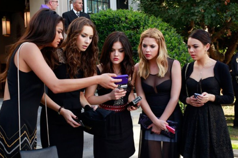 The Pretty Little Liars girls crowd around a mobile phone with surprised faces