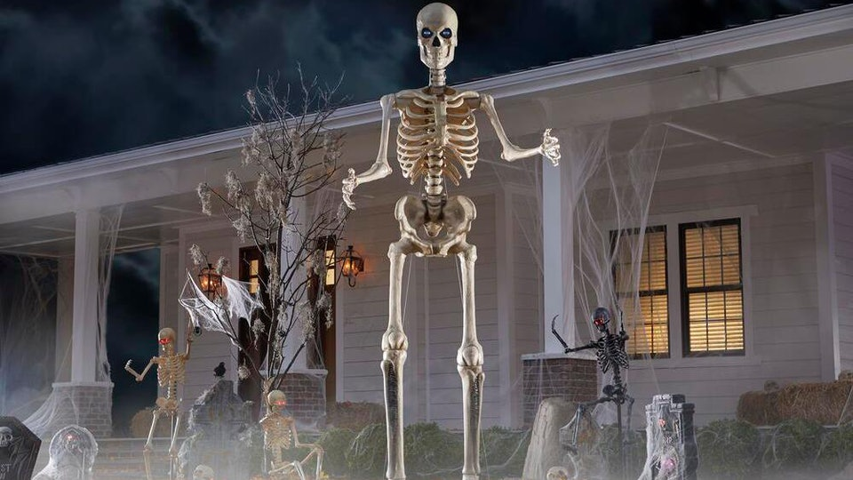 An image of a huge skeleton with glowing red eyes in front of a white house.