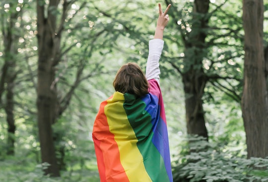 woman wrapped in rainbow flag giving peace sign in the woods