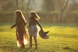 Two tweens in halloween costumes running through a lawn