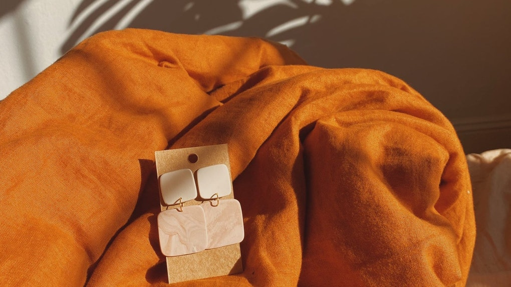 A pair of Bohemian polymer clay earrings sit on an orange blanket next to the shadow of a palm leaf.
