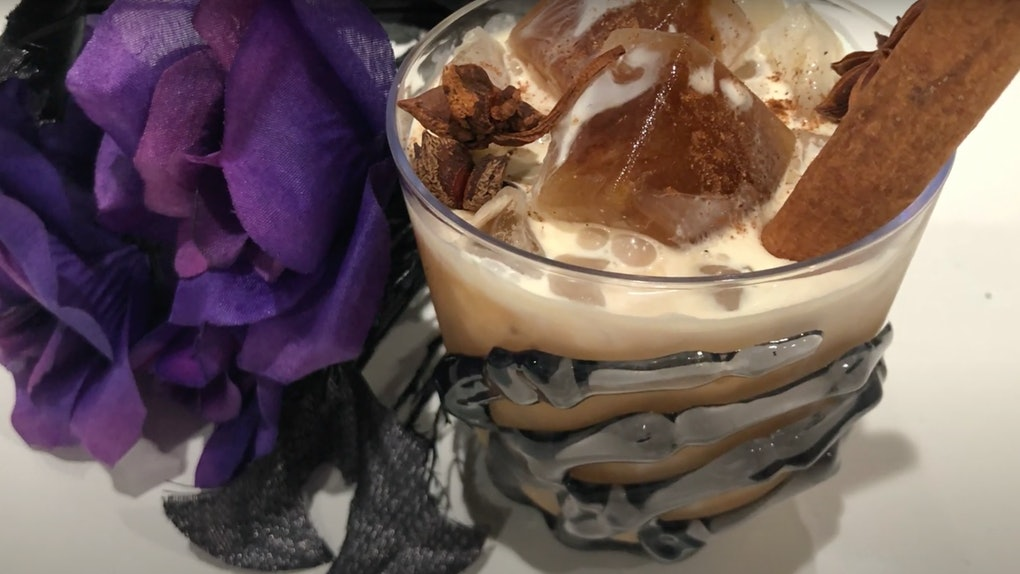 A halloween coffee drink sits on the table next to purple flowers in a skeleton hand cup.