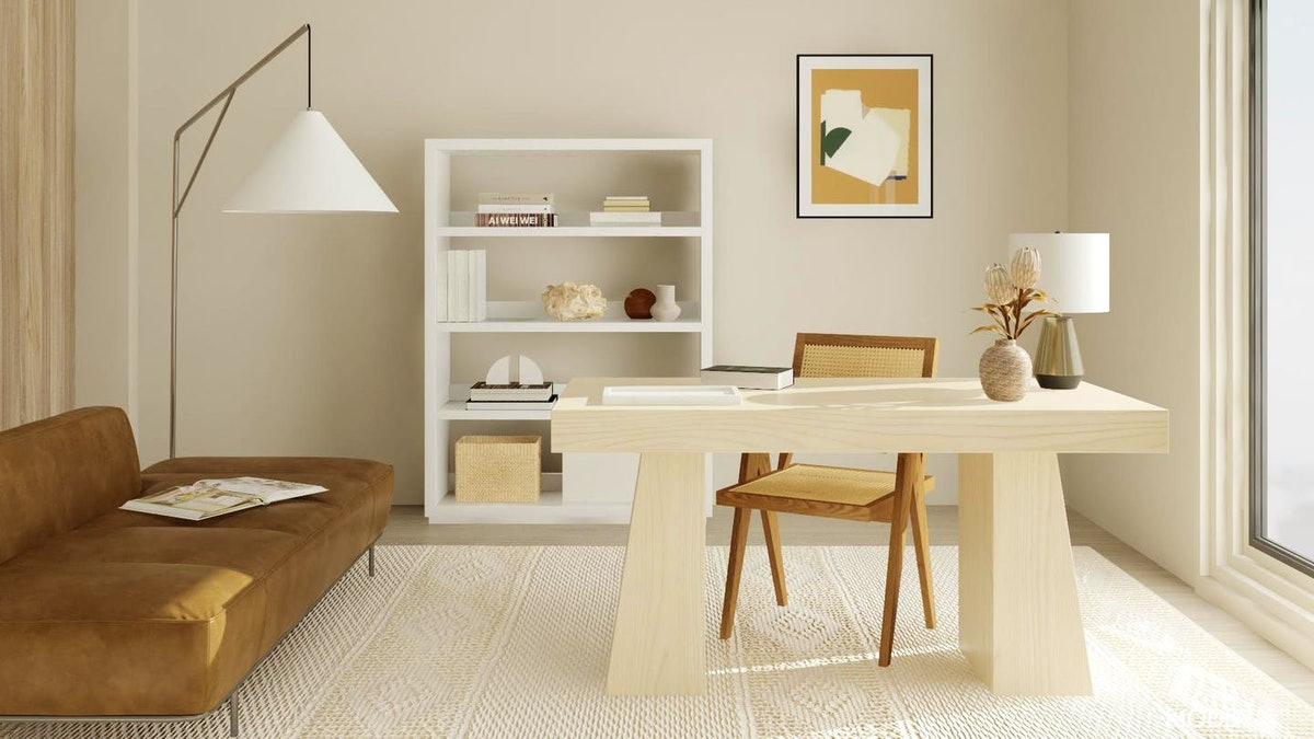 A decorated home office has minimalist feel with a white bookshelf and wooden desk.