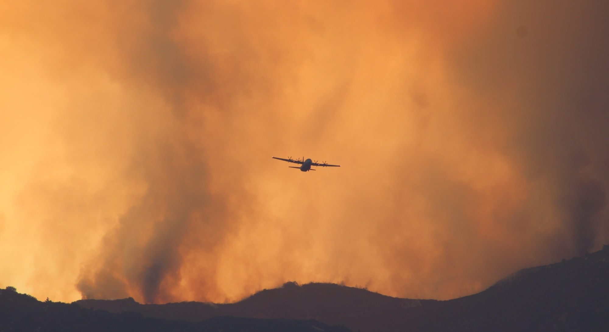 Low Angle View Of Silhouette Airplane Flying Against Sky During Wildfire