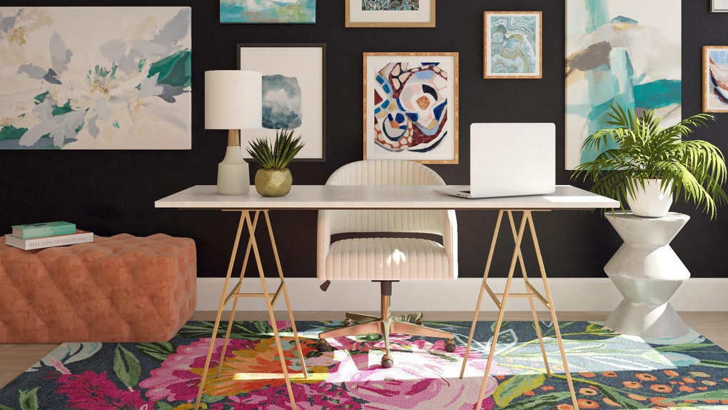A decorated home office has a colorful rug and artwork hung all over the wall.