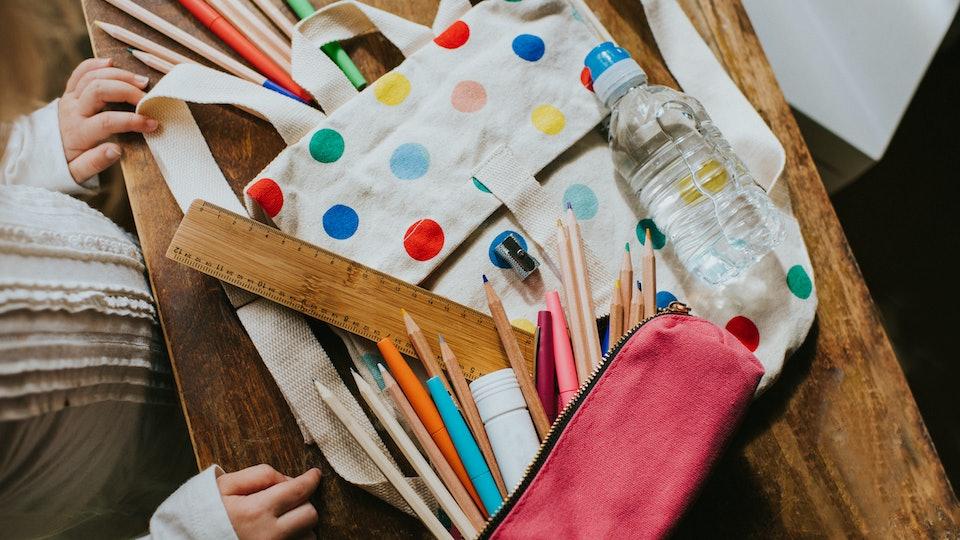 a little girl going through her school supplies