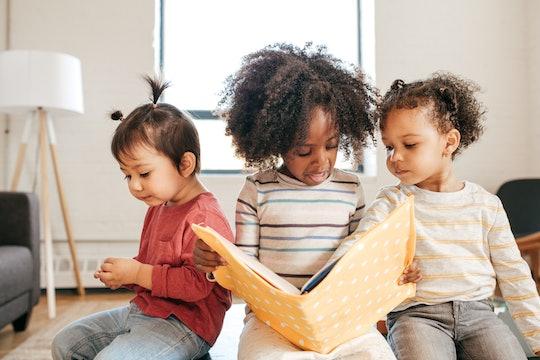 three kids reading a book