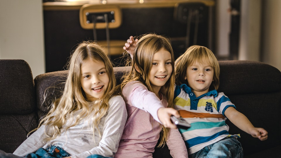 Siblings sitting on the couch watching Television