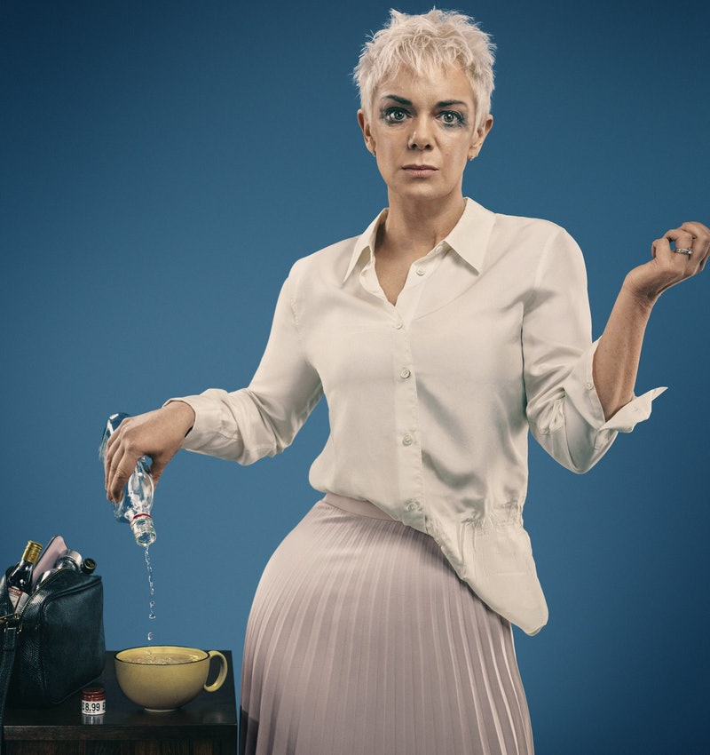 Victoria Hamilton as Anna with pixie cut silver-blonde hair and mascara around her eyes, wearing a white shirt and a lilac pleated skirt, pouring a bottle of spirit into a mug.