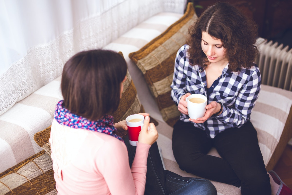 Two women drinking coffee on the couch