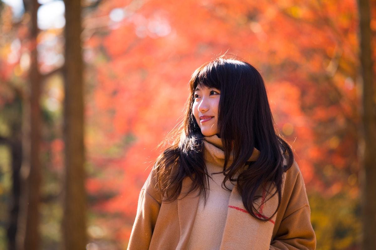 Young woman walking in autumn/fall foliage