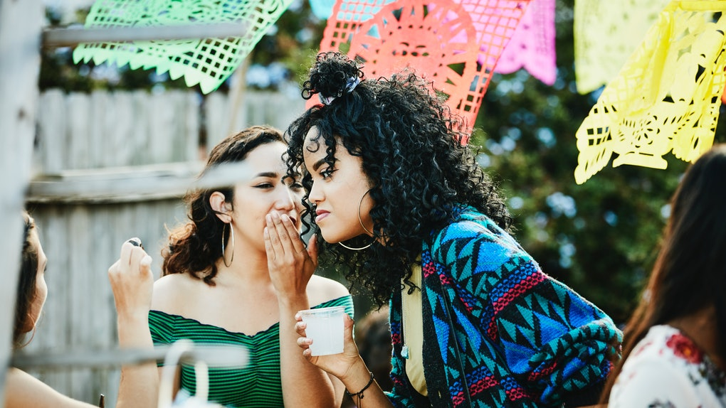 Woman whispering to friend during backyard party