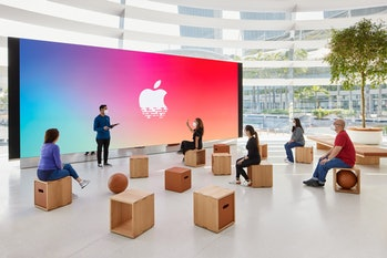 People watch a large projection screen with the Apple logo.