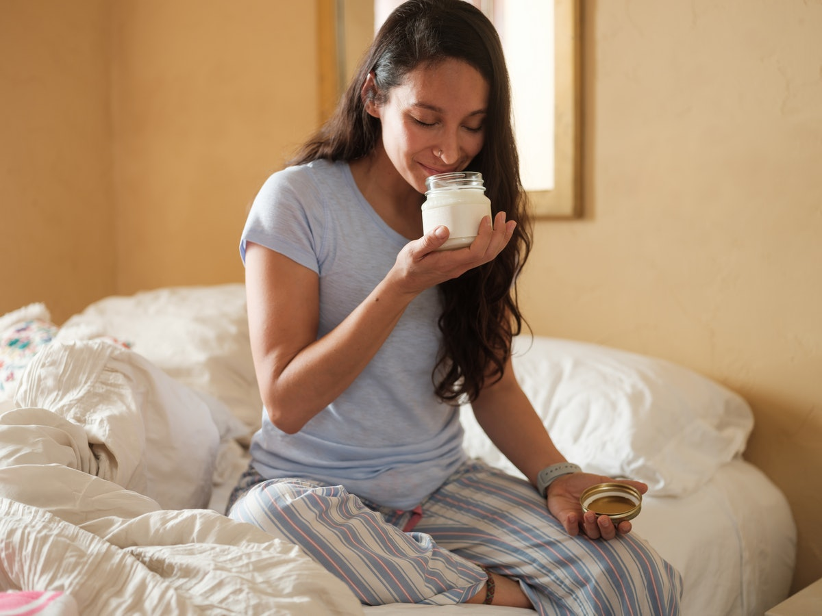 Young woman smelling candle