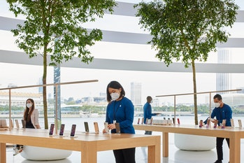 Four Apple employees in face masks adjust iPhones at the new Marina Bay Sands store.