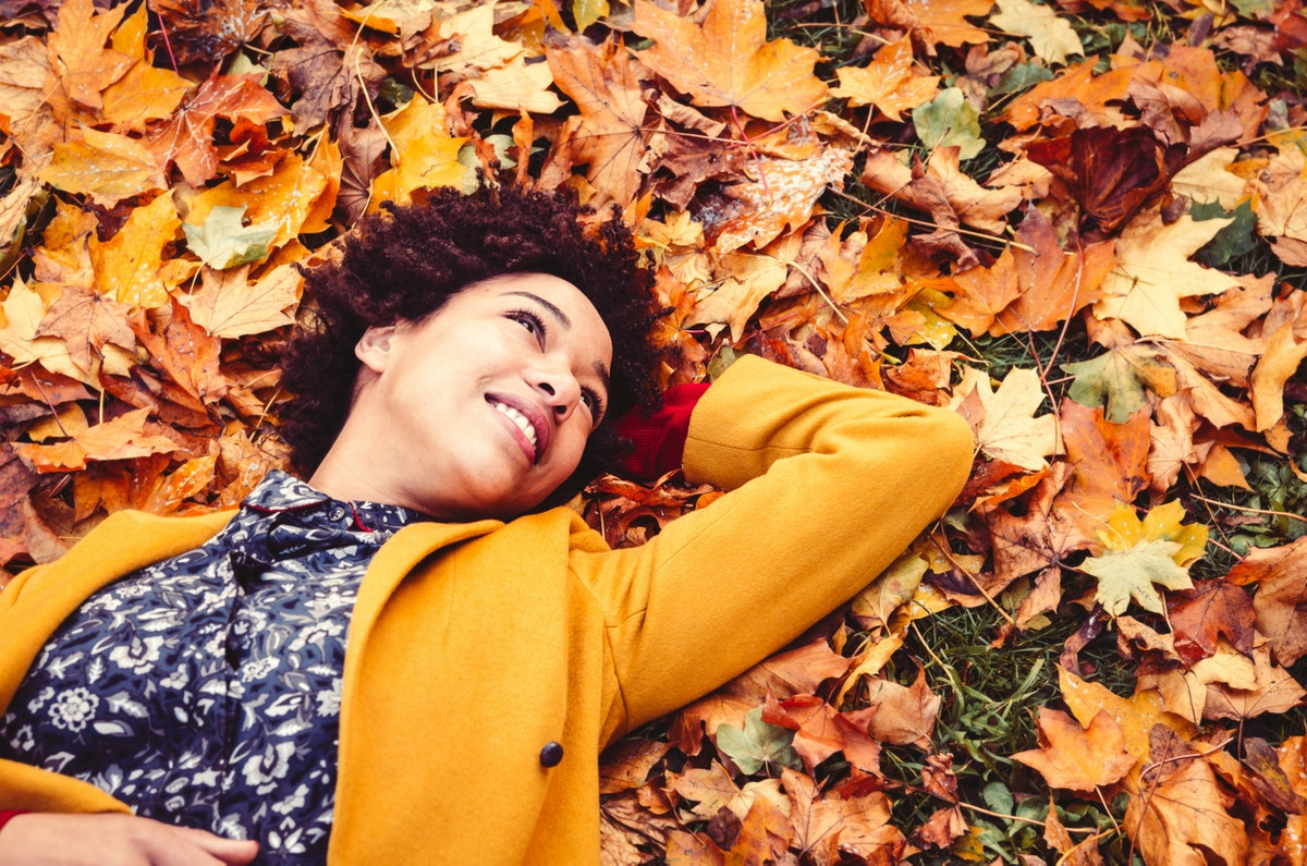 Young woman lying down on autumn leaves