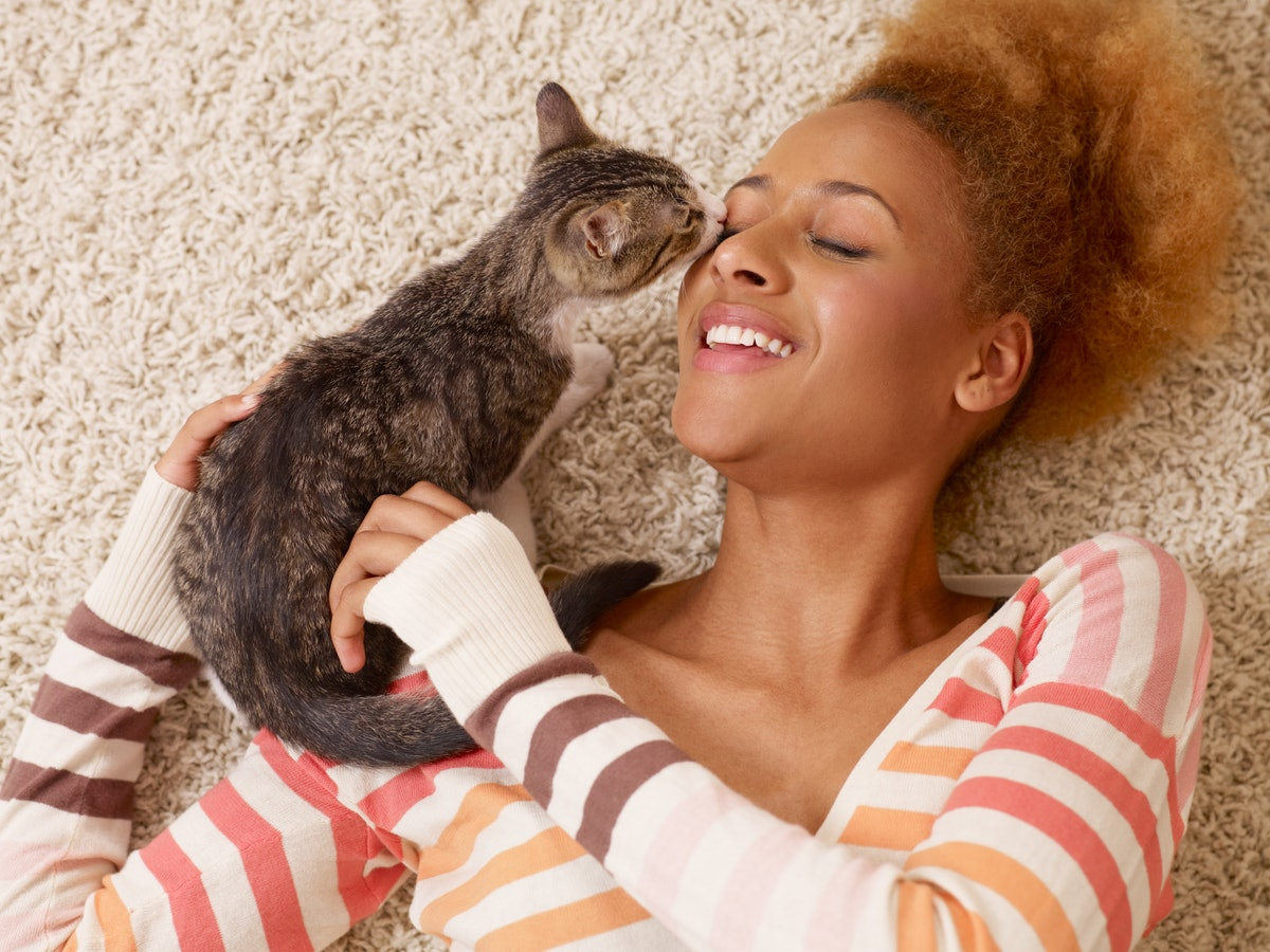 Young woman laying on carpet with cat