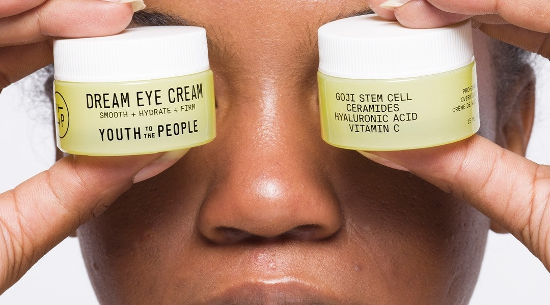 Youth To The People's Dream Eye Cream held by model.
