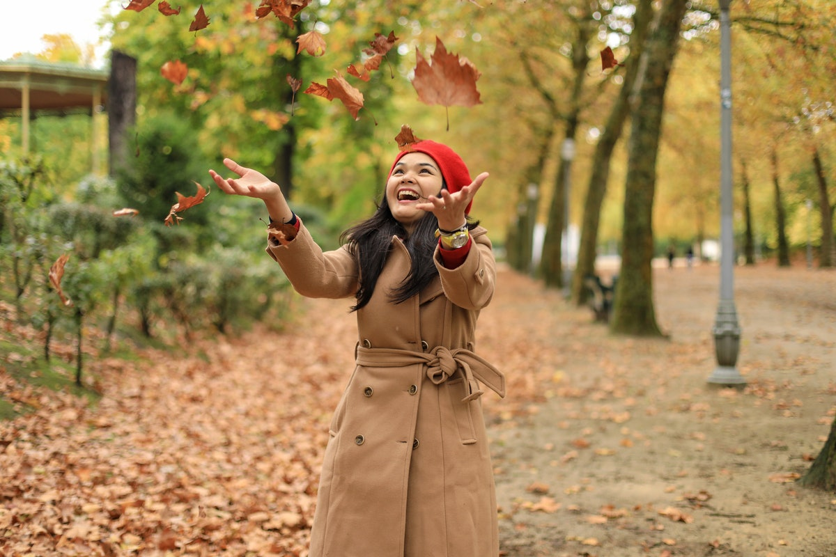 Young Asian woman playing in autumn leaves