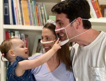 A mother and father are smiling brightly at their infant with transparent face masks on. The infant is beaming in return.