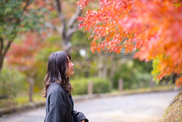 Young woman looking at autumn leaves