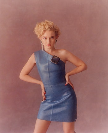 Julia Garner with a Motorola Razr clinging to her leather dress.
