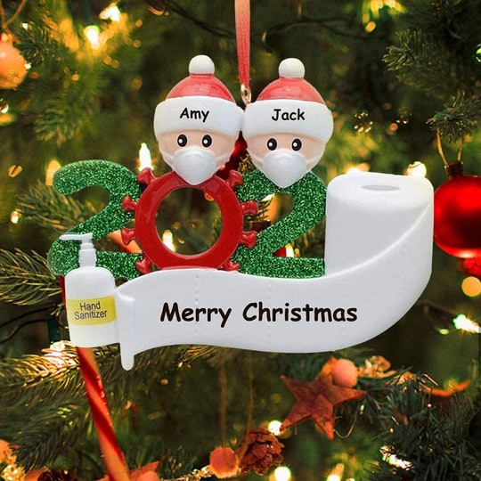 An image of two kids wearing Santa hats and surgical masks above a 2020 banner beside a hand sanitizer bottle.
